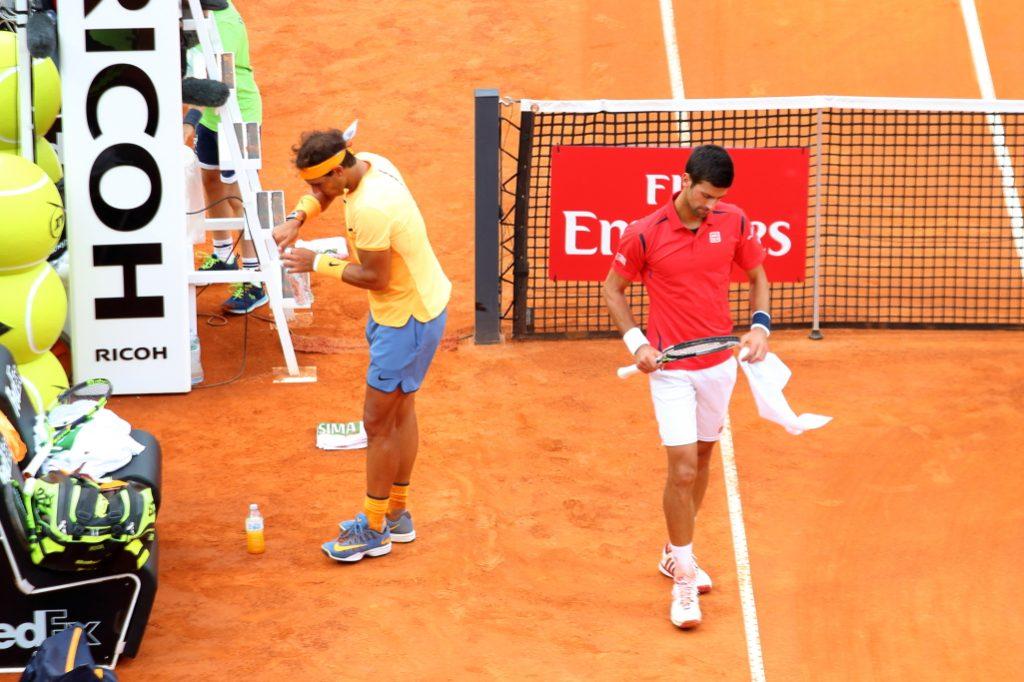 Novak passa mentre Rafael si sta sistemando le sue bottigliette (con la precisione milimetrica)